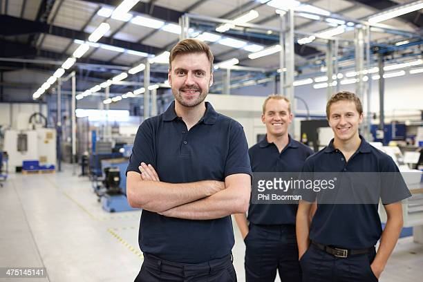 Portrait of three workers in engineering factory