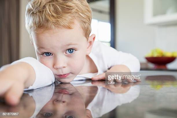 Portrait of three year old boy leaning forward on kitchen bench