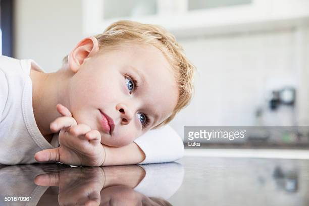 Portrait of three year old boy leaning on kitchen bench