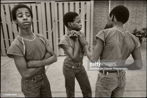 Portrait of three young boys, in matching outfits as they wait for a breakdancing competition to begin, Hayward, California, 1985.
