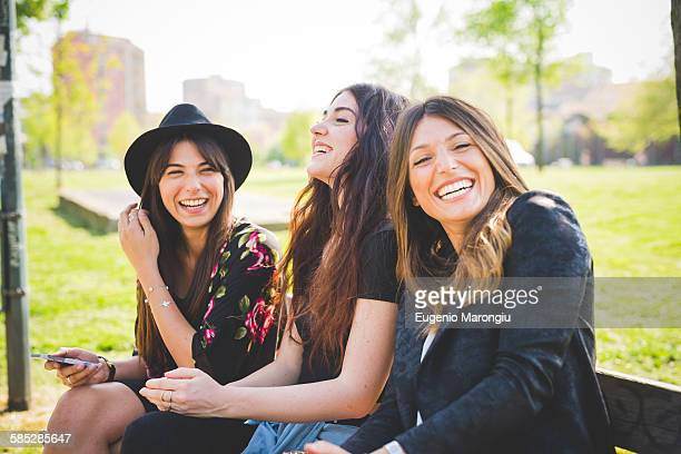 portrait of three young female friends laughing in park - fedora stock pictures, royalty-free photos & images