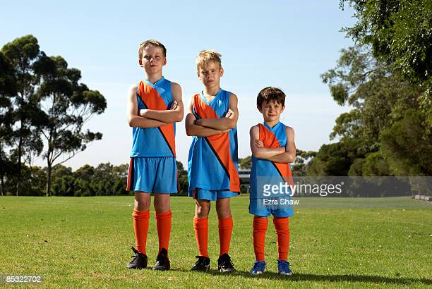 Portrait of three young football players