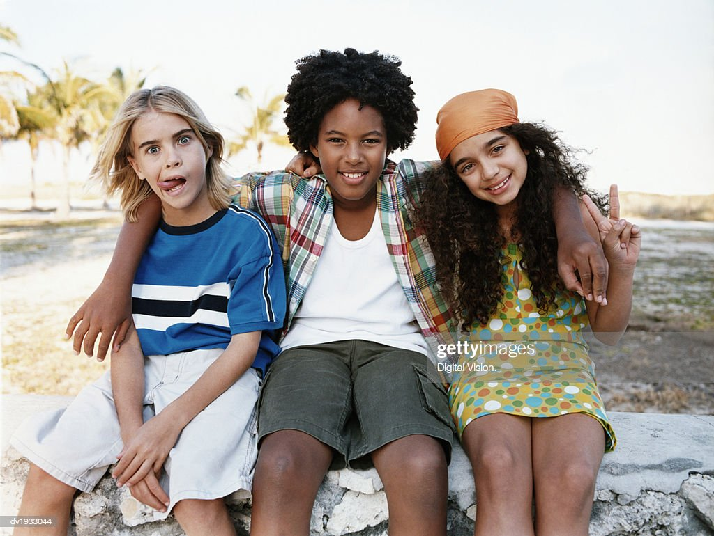 Portrait of Three Young Friends Sitting Together on a Stone Wall : Stock Photo