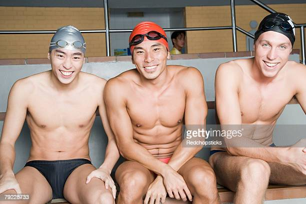 portrait of three young men sitting together and smiling - young men in speedos stock photos and pictures