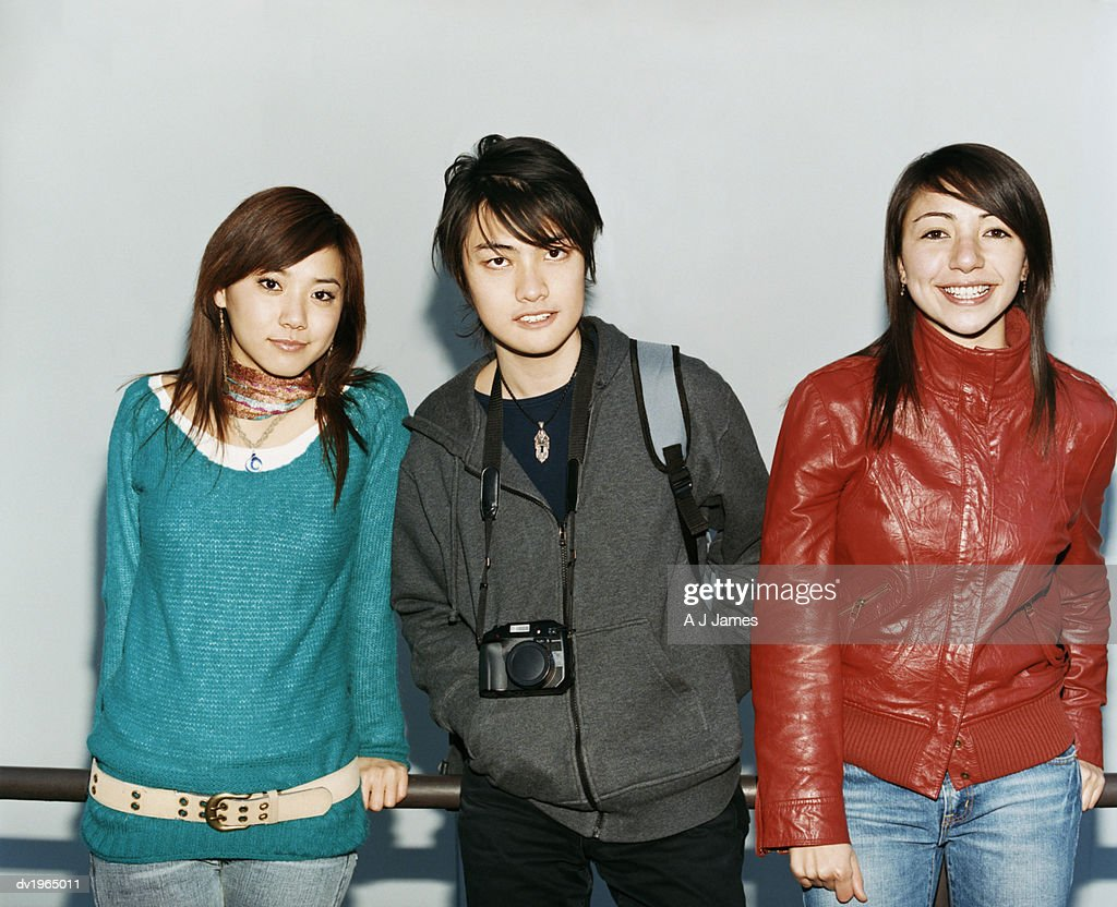 Portrait of Three Young People Leaning Against a Metal Railing : Stock Photo