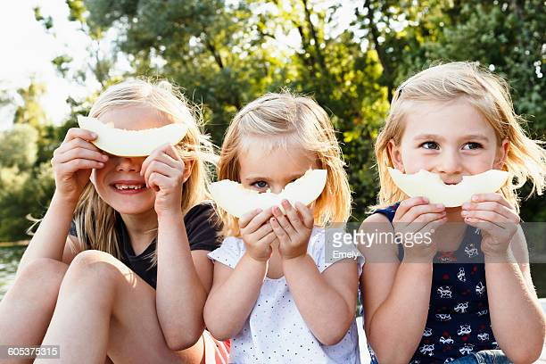 portrait of three young sisters holding smiling melon in front of face in park - teilen stock-fotos und bilder