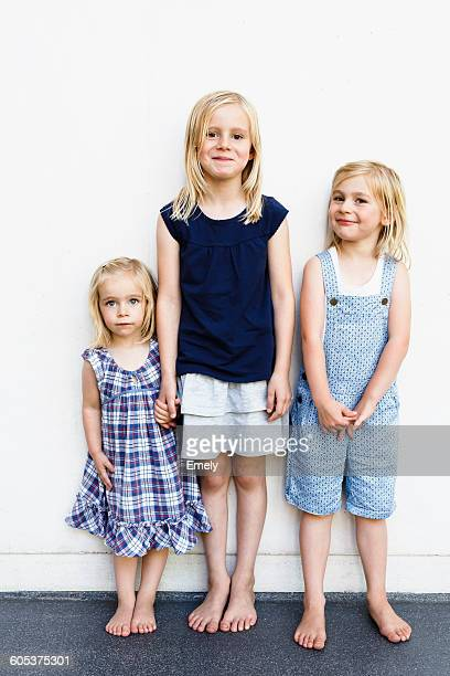 Portrait of three young sisters standing in front of white wall