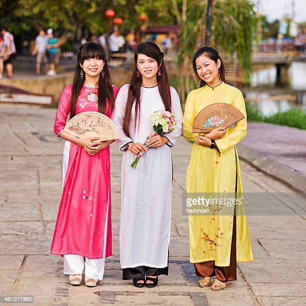 Portrait of three young Vietnamese women wearing ao dai