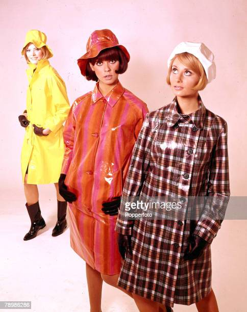 1966 A portrait of three young women all wearing fashionable coloured plastic raincoats and matching hats all are smiling towards the camera
