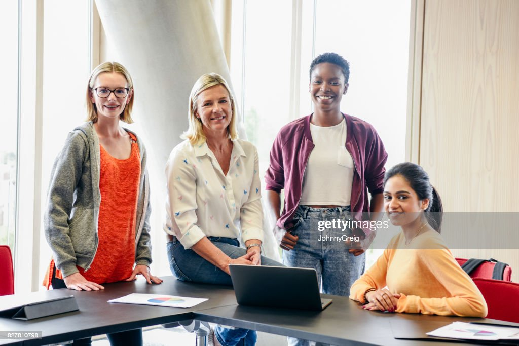 Retrato de tres mujeres jóvenes en el colegio con su maestra madura : Foto de stock