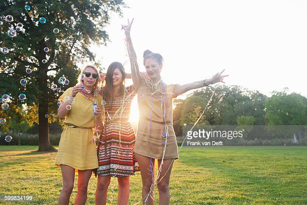 Portrait of three young women friends wrapping themselves in streamers at party in park