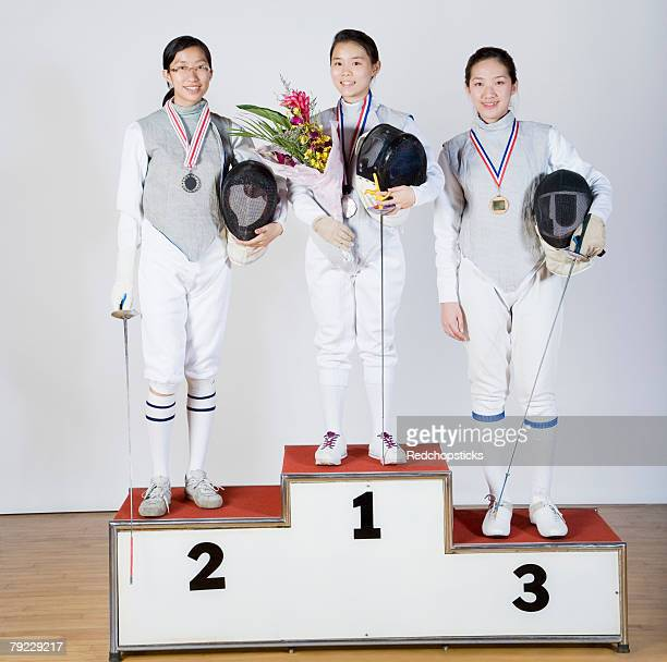 Portrait of three young women in fencing costumes standing on a winner's podium