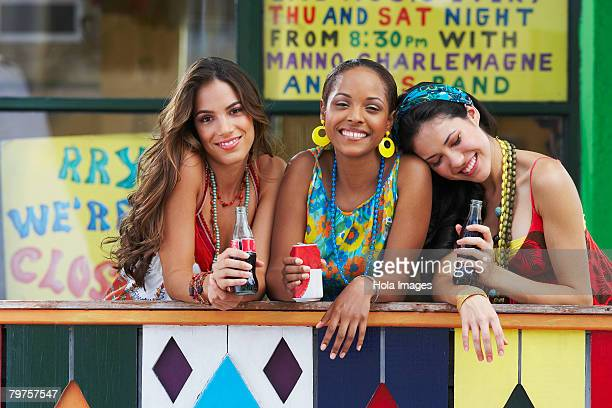 Portrait of three young women leaning on a railing and holding cold drinks