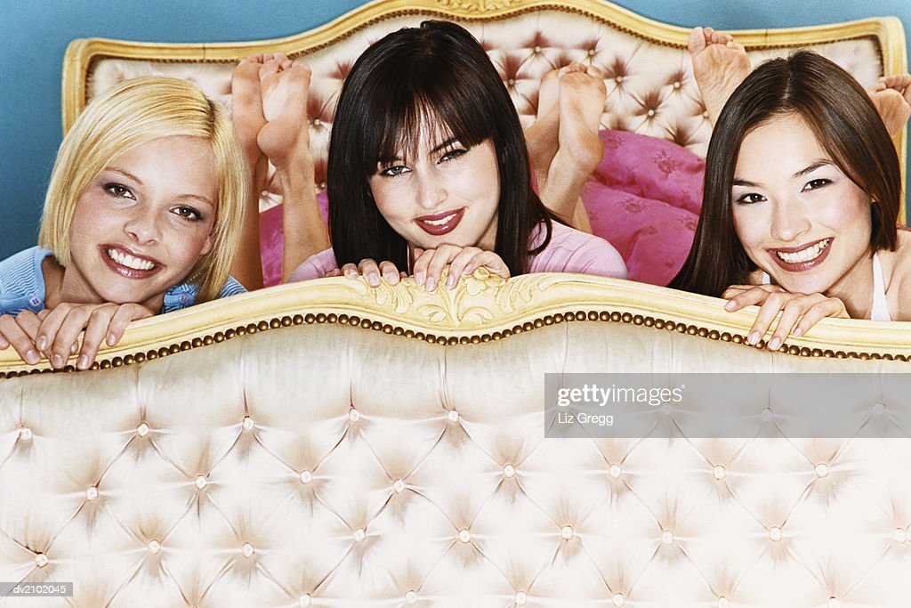 Portrait of Three Young Women Lying on a Luxurious Bed : Stock Photo