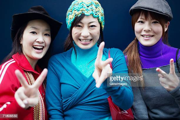Portrait of three young women making the peace sign