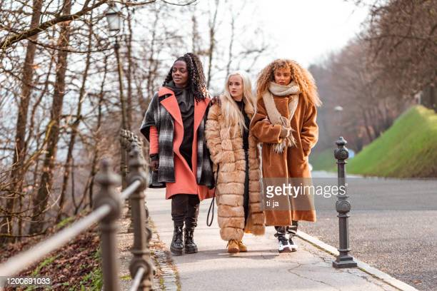 portrait of three young women outdoors stock photo - fur coat stock pictures, royalty-free photos & images