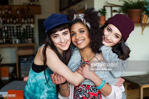 portrait of three young women smiling in cafe - only young women stock pictures, royalty-free photos & images