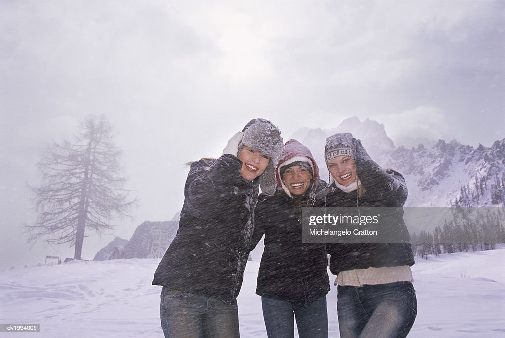 Portrait of Three Young Women Standing as Snow Falls in the Mountains : Stock Photo