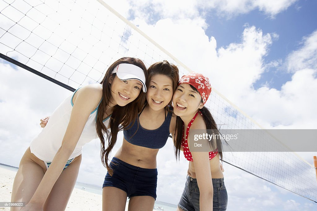 Portrait of Three Young Women Standing by a Volleyball Net : Stock Photo