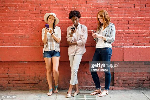 Portrait of three young women using mobile phones