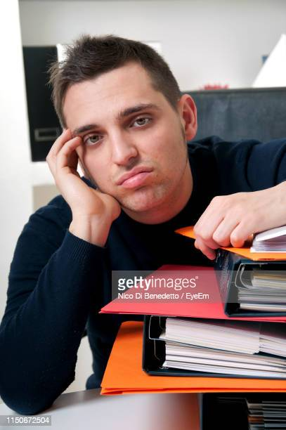 portrait of tired businessman sitting by files in office - benedetto photos et images de collection
