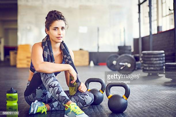 Portrait of tired female athlete sitting by kettlebells in gym