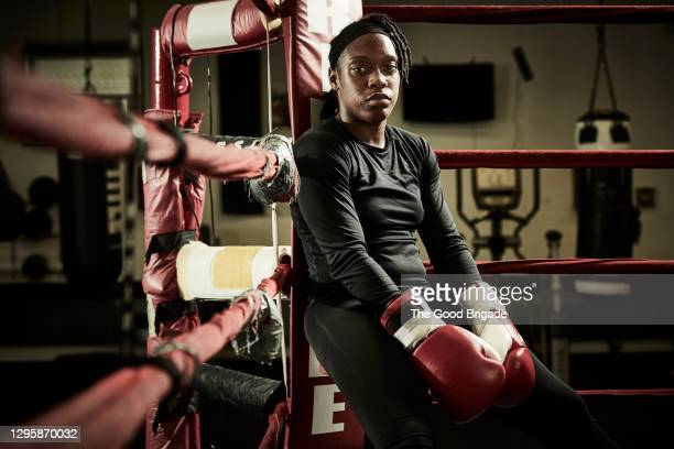 portrait of tired female boxer sitting in boxing ring - 格闘技 ストックフォトと画像