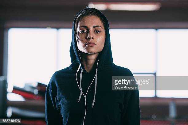 portrait of tired woman wearing hooded shirt standing at gym - atleta imagens e fotografias de stock