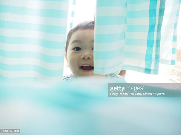 Portrait Of Toddler Hiding Amidst Curtains At Home