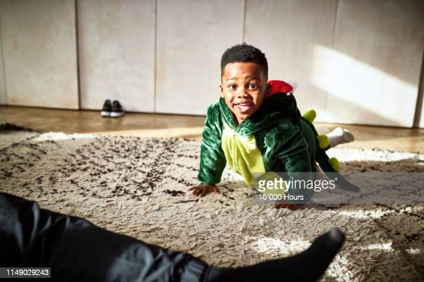 portrait of toddler in dragon costume crawling on rug - boys stock pictures, royalty-free photos & images