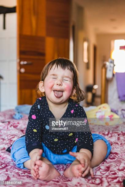 portrait of toddler sitting barefoot on bed sticking out tongue - ピンクの頬 ストックフォトと画像