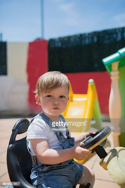 Portrait of toddler sitting on bobby car