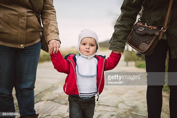 Portrait of toddler walking hand in hand with two women