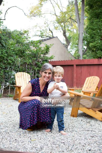 portrait of toddler with his god mother on pebbled lounge area. - pasadena california stock pictures, royalty-free photos & images