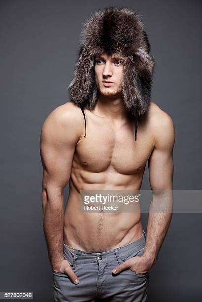Portrait of topless man wearing fur hat