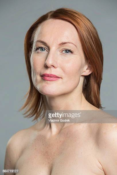 Portrait of topless mature woman against gray background