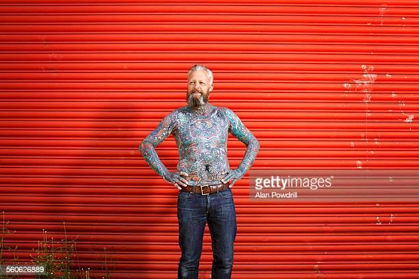Portrait of topless tattooed bearded man