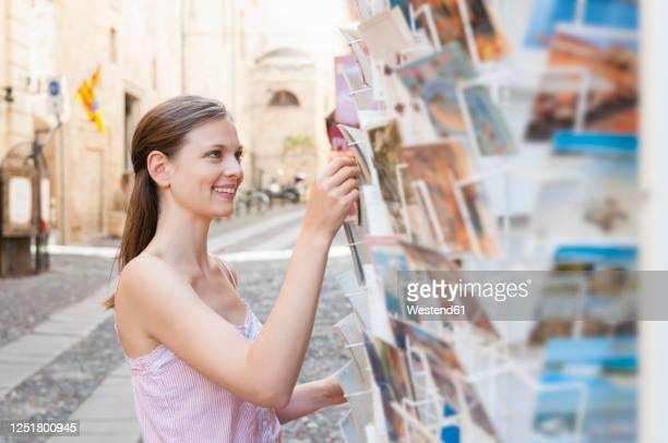 portrait of tourist choosing postcards in the city, sardinia, italy - postcard stock pictures, royalty-free photos & images