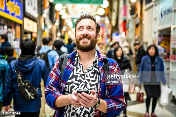 portrait of tourist in patterned shirt looking up on busy street - turista foto e immagini stock