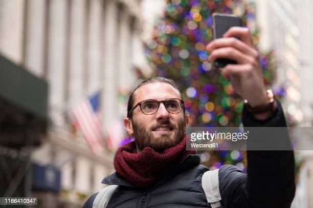 portrait of tourist taking selfie with smartphone in front of lighted christmas tree, new york city, usa - patriotic christmas stock pictures, royalty-free photos & images