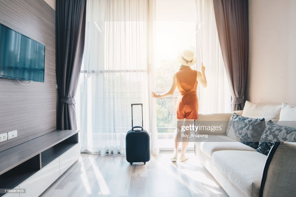 Portrait of tourist woman standing nearly window, looking to beautiful view with her luggage in hotel living room after check-in. : Stock Photo