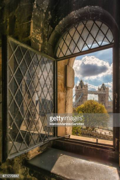 portrait of tower bridge from an old window at tower of london - tower of london stock pictures, royalty-free photos & images