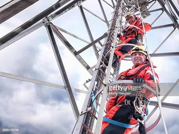 Portrait of tower workers climbing radio tower on offshore windfarm, low angle view