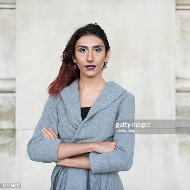 Portrait of transgender female facing camera, arms folded
