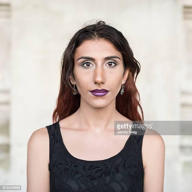 Portrait of transgender female wearing black top looking towards camera