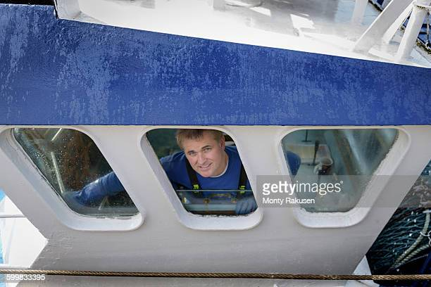 Portrait of trawler captain looking out of window of wheel house