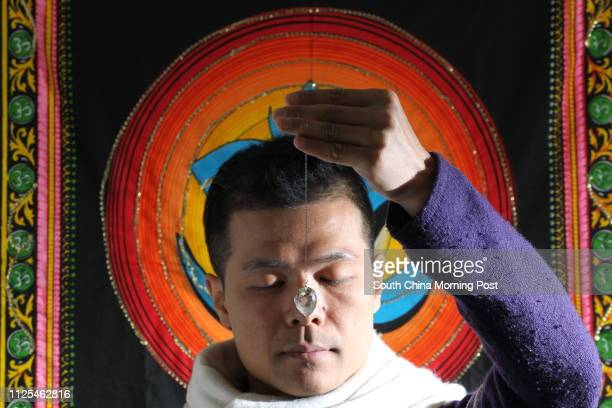 Portrait of Tsang Mantung with spiritual name Sol Manzana a dowser holding the pendulum at his home in Lam Tsuen 07JAN13