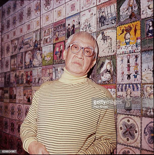 A portrait of Tsougharu Foujita standing in front of a wall covered with his small tilelike paintings France 1958