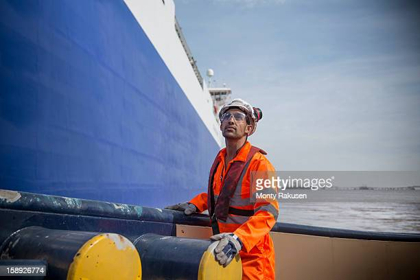 Portrait of tug worker looking up on tug at sea