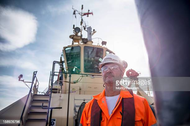 Portrait of tug worker wearing hard hat and protective goggles on tug